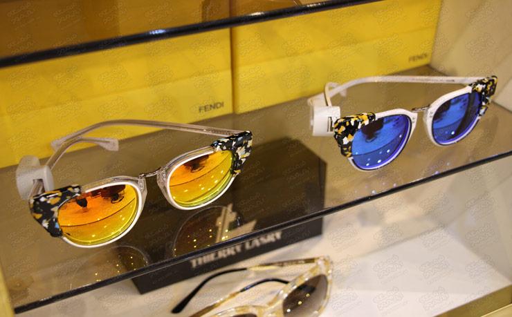 تگ-آچاری-عینک-روی-دو-عینک-آبی-و.زرد-در-پشت-ویترین